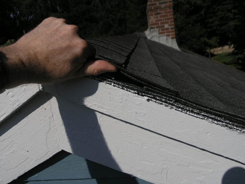 Holding roof shingles back with fingers