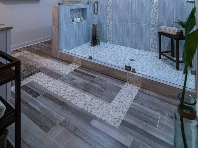 View of large shower and porcelain tile flooring that looks like hardwood