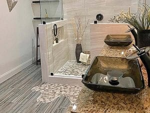 Bathroom floor idea of lighter hardwood replica with mosaic splash